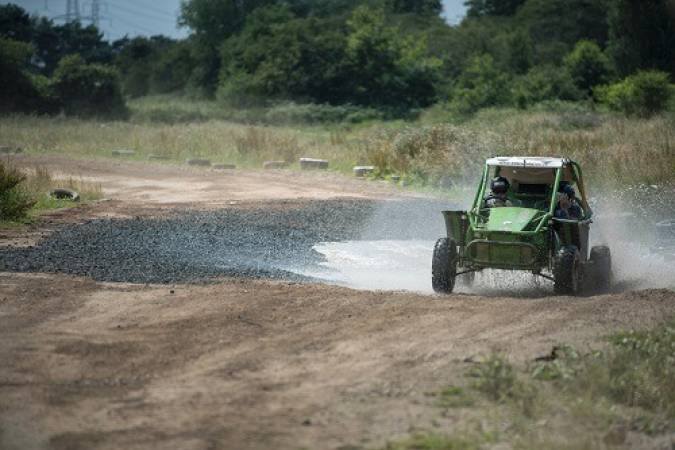 green buggy travelling through water and waste ground
