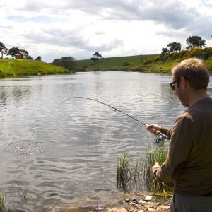 man trout fishing at waters edge