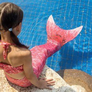 girls sitting at edge of pool in mermaid costume