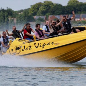 people with saftye gear on a yellow speed boat on the water