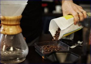 someone pouring out coffee beans