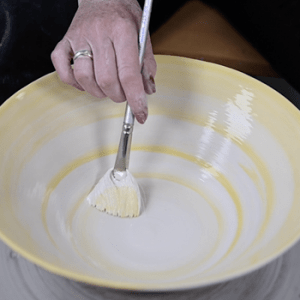 lady painting a ceramic bowl