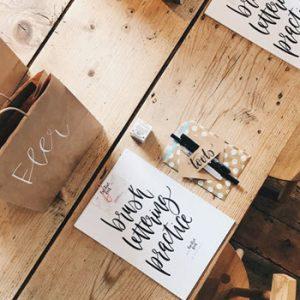 Brush lettering kit on wooden table