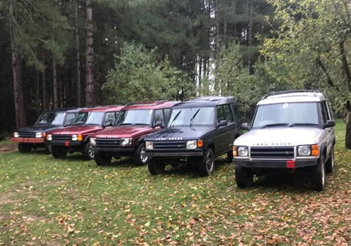 5 landrovers on grass