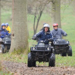 men quad biking in forest
