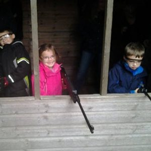 children learning to shoot with rifles