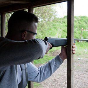 man aiming gun at rifle shooting experience