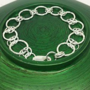 silver charm bracelet on green dish