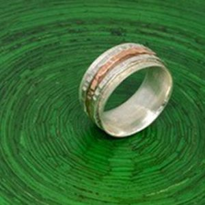 silver and gold ring on green background