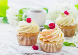 cupcakes with raspberries on top