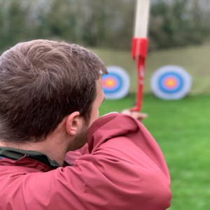 Man with a bow and arrow pointing at target