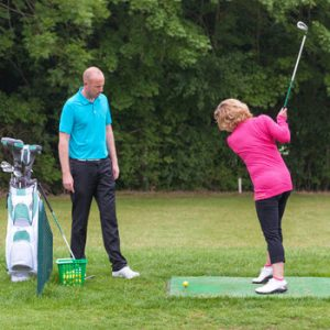 lady with golf club at golf lesson