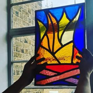 stained glass window held up against a window