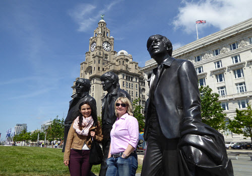 two girls next to bronze statue in Liverpool