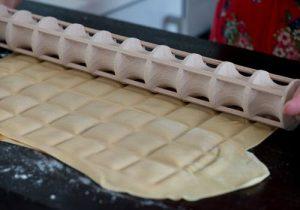 wooden pasta roller cutting fresh pasta