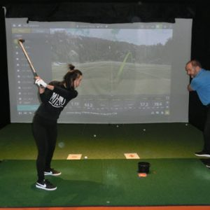 lady swinging golf club at St Andrews Indoor golf centre