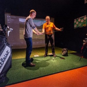 Black Titleist Golf Bag man with golf club indoor getting tuition
