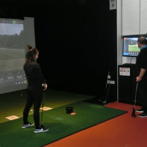 Female standing indoors getting golf lesson from another man