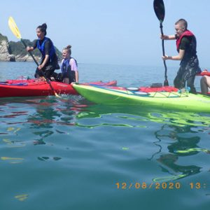 1 red 1 green kayak at sea with 2 people in each paddling