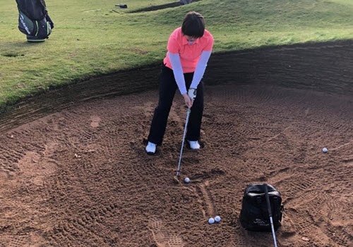 person in pink golf gear with about to swing club in bunkers
