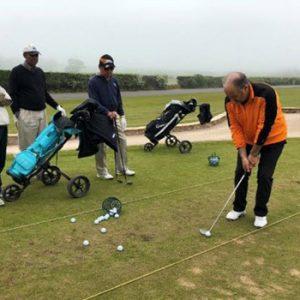 3 men on golf practice range watching man in orange top hit golf ball