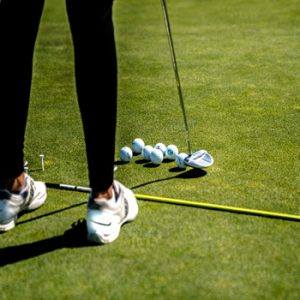 womans legs in black with white trainers putting golf balls