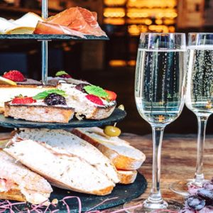 Italian afternoon tea on stand with two glasses prosecco