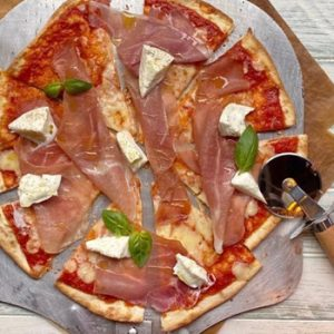 salami pizza with pizza cutter