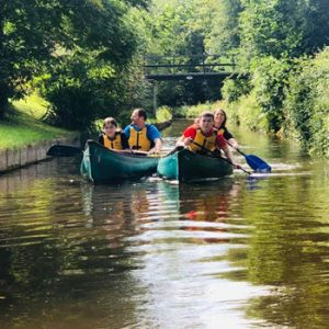 2 green canoes with people in safety gear paddling along canal