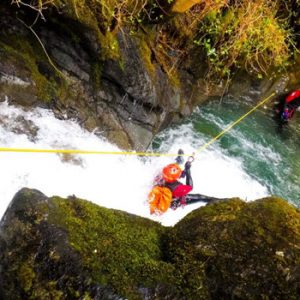 Person on a zip slide going into water at side of hill