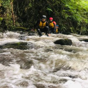 two people coming down the river rapids in safety gear
