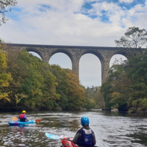 2 canoes on River paddling towards aqueduct