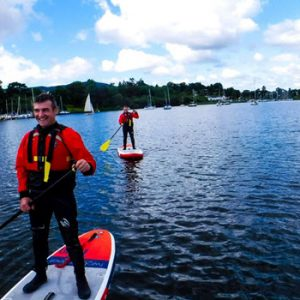 Man in red black wet suit on paddle board on Lake