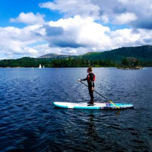 Man standing in wet suit on a paddleboard on lake