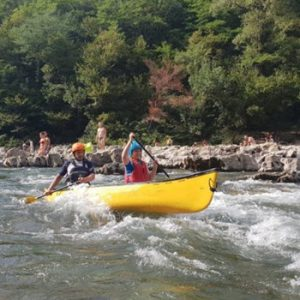 people paddling in yellow canoe in river rapids