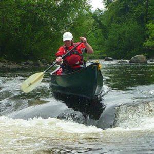 person in dark green canoe on river rapids