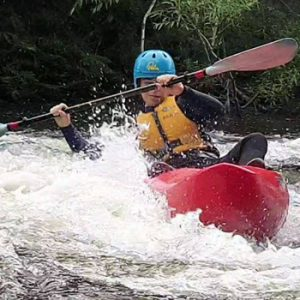 person paddling a kayak in river rapids