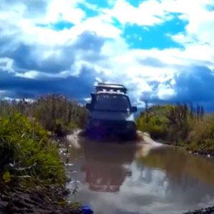 jeep in muddy water down a bank