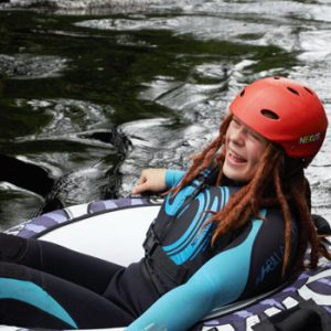 girl in wet suit and safety equipment in a dingy on water