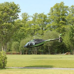 helicopeter landing at grass helipad in estate surrounded by trees