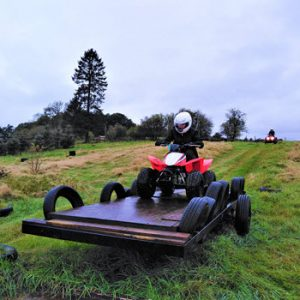 person on quad bike in safety gear on a wooden ramp in countryside