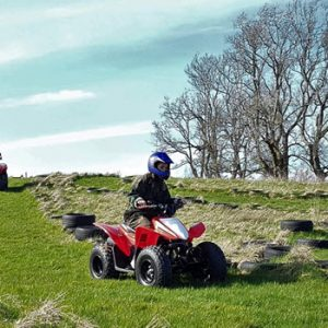 quad bikes with people in them on hill