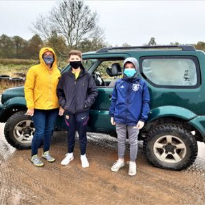 Woman and 2 chidlren in front of jeep on wet mud terrain