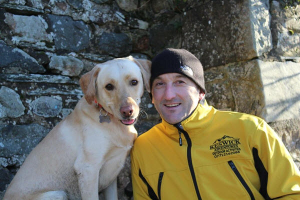 man in yellow top and black hat with yellow labrador