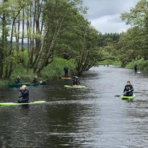 2 people paddling in canoes in the