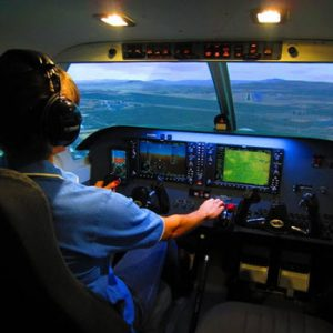 man inpilot gear in cockpit on runway