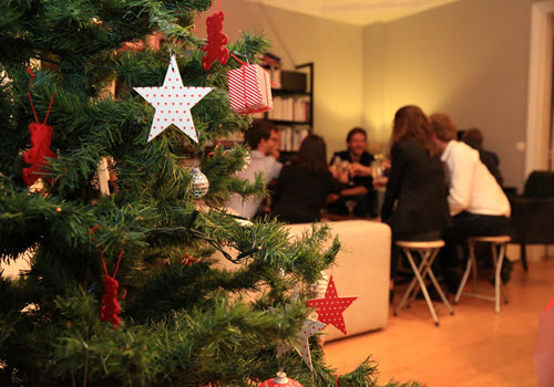 Christmas Tree with star and family in background opening presents