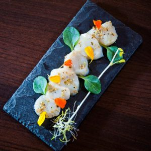4 scallops on a slate with salad decoration