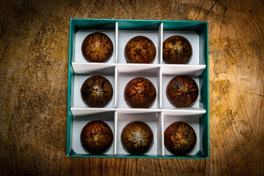 3 rows of chocolate truffles in a green box