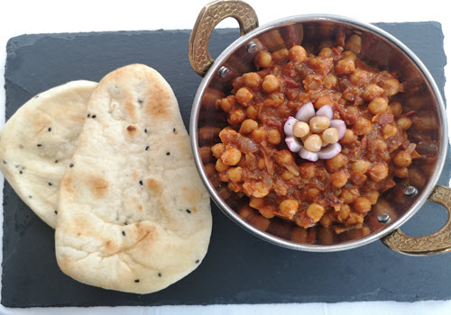 nan bread on slate & Chickpea Curry in silver dish